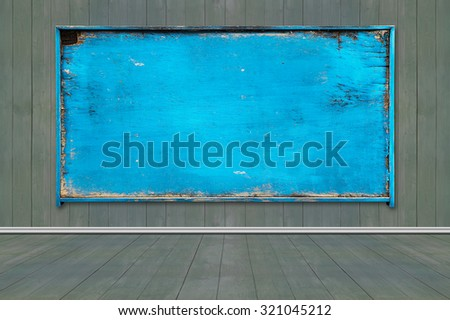 Old blank blue weathered noticeboard on wooden wall and floor background. - stock photo