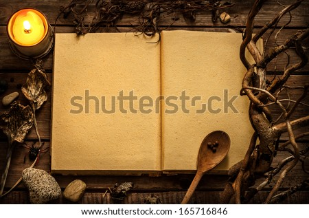 Old blank open witchcraft or magic recipes book with candle and alchemy ingredients around. Dark mysterious rustic background with text space. - stock photo