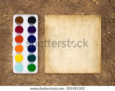 Old blank paper and paints on brown weathered  background - stock photo