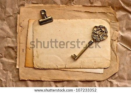 old blank paper sheets with clip and vintage key - stock photo
