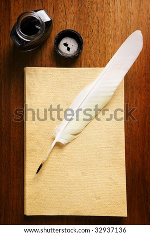 Old blank paper with quill pen and ink on wooden table