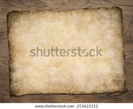 Old blank parchment treasure map on wooden table - stock photo
