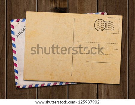 Old blank post card and envelope, on wooden table. - stock photo