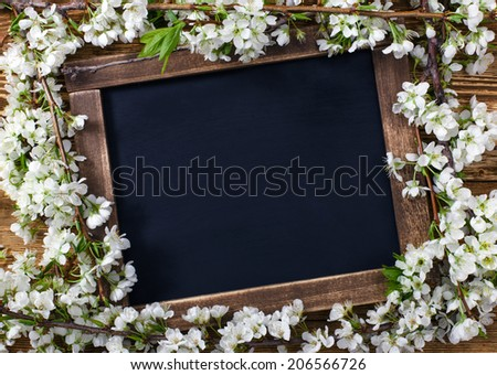 Old blank vintage school slate or chalkboard lying on an old rustic wooden background with dainty white flowers in two corners ready for your text or message - stock photo