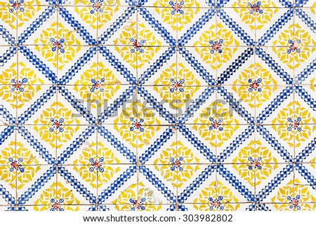 Old blue and yellow azulejos on the building's exterior in Lisbon, Portugal. - stock photo