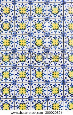 Old blue and yellow azulejos on the building's exterior in Lisbon, Portugal. It is a form of Spanish and Portuguese painted tin-glazed ceramic tilework. - stock photo