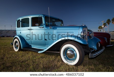 old blue car with whitewall tires on the grass of classic cars exhibition in florida