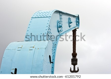 Old blue crane with rusty chain and hook on harbor with cloudy sky - stock photo