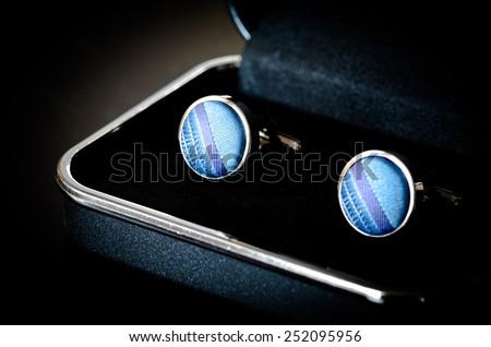 old blue cufflinks on black box - stock photo