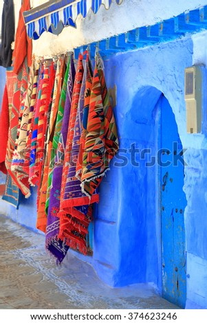 Old blue door and traditional textiles in the old Medina of Chefchaouen, Morocco - stock photo