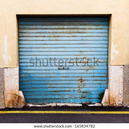 Old, blue door of garage - stock photo