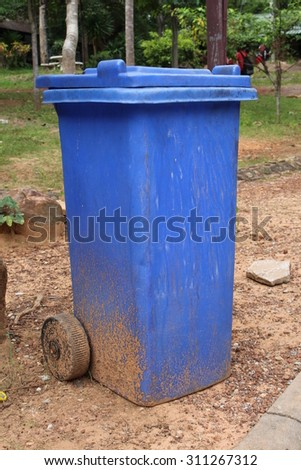 old blue garbage cans on the street