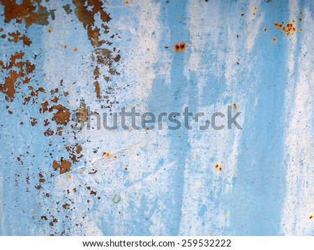 Old blue grunge material. Peeling paint and rust stains. Shallow depth of field. - stock photo