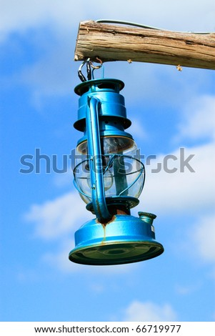 Old blue lantern hanging by wood on the sky - stock photo