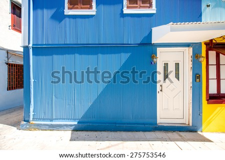 Old blue painted facade with white door in Greece