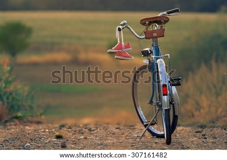Old blue retro bicycle in the village  - stock photo