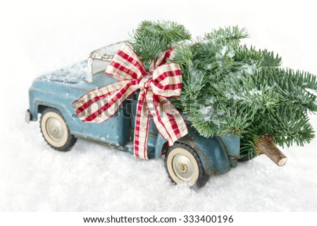 Old blue toy truck carrying a green Christmas tree covered with snow and a red ribbon on white snowy background - stock photo
