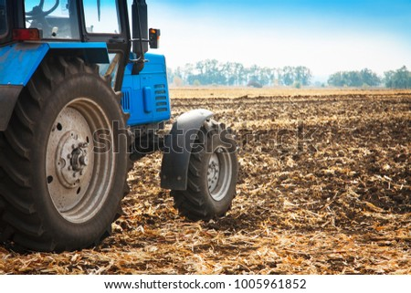 Old blue tractor in a empty field on a bright sunny day. Agricultural machinery, field work.