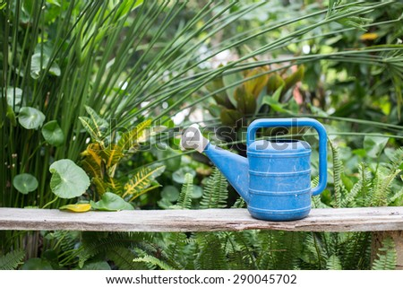 old blue watering can in the garden - stock photo