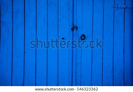 Old blue wooden front door, without door handles. Vintage door in old house.