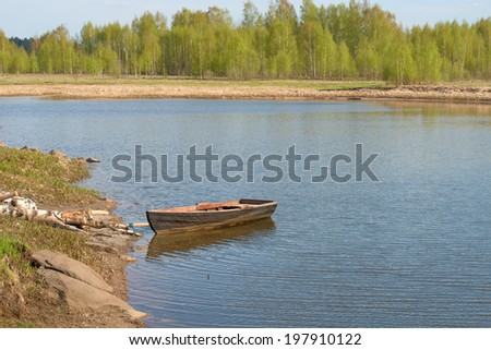 Old boat by the river on a leash - stock photo