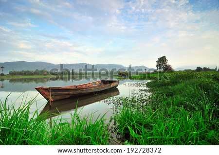 Old boat in a calm lake on a beautiful sunny day