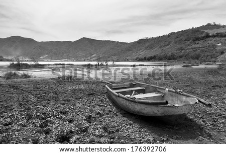 old boat on dry lake black and white photo - stock photo