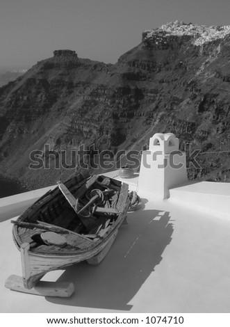 Old boat on roof in Santorini - stock photo