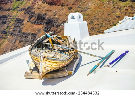 Old boat on roof of house and colorful old staircase in Santorin - stock photo