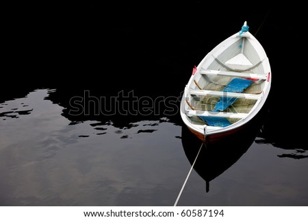 old boat on surface of dark water - stock photo