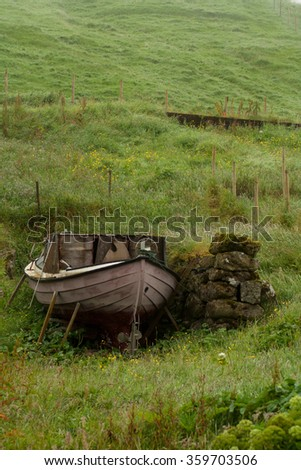 Old boat on th e green grass. Close up and vertical image. - stock photo