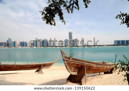 Old boat on the background of skyscrapers in Abu Dhabi, United Arab Emirates - stock photo