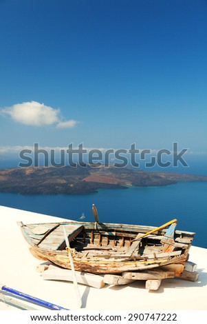 Old boat on the roof of a private villa in Firostefani, Santorini, with a perfect view of the volcanic island