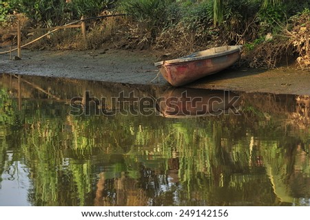 Old boat reflection in the swarm  - stock photo