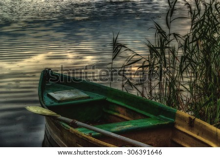 Old boat with an oar on the shore in the reeds evening twilight hdr  - stock photo