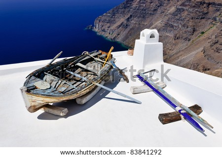 Old boat with oars located on the white roof. Santorini, Greece - stock photo