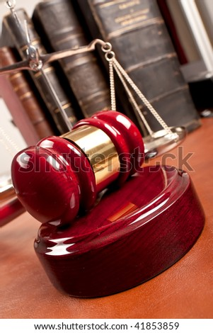 Old book and gavel on leather desktop - stock photo