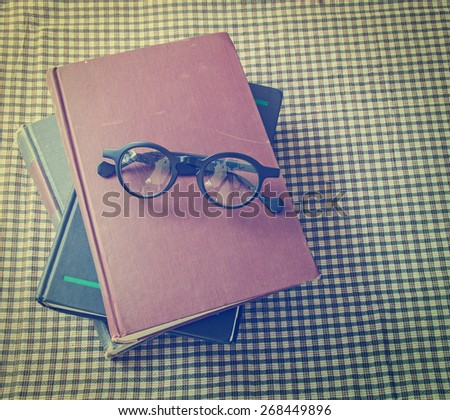 old book and glasses on table - stock photo