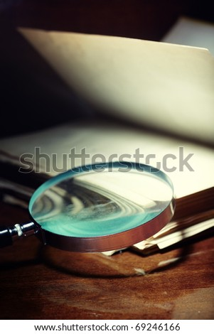 Old book and magnifier on a dark background as a symbol of scientific study - stock photo