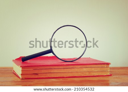 old book and magnifying glass. room for text. image is retro filtered. - stock photo