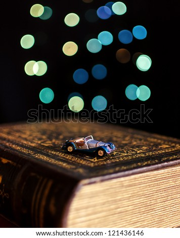 Old book and miniature car on bokeh lights background - stock photo