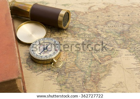 Old book and old spyglass and old compass on vintage map world discovery concept