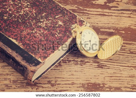 Old book and watch on wooden background - stock photo