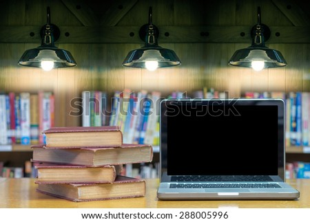 old book on the desk in library with laptop and Luxury lighting decoration - stock photo