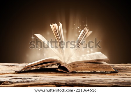 Old book on wooden planks with blur shimmer background - stock photo