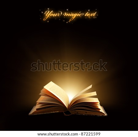 Old book. Opened magic book with magic light on a black background. - stock photo