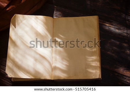 Old book opened on wooden table.