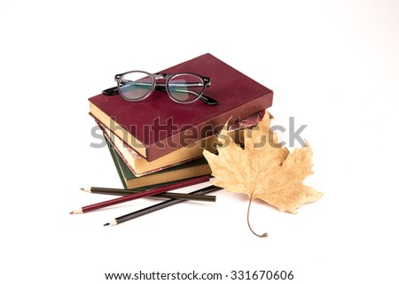 Old book, vintage glasses, autumn leave and color pencils isolated on white background  - stock photo