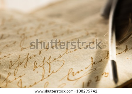 Old book with feather pen - stock photo
