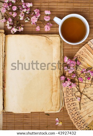 Old book with green tea - stock photo